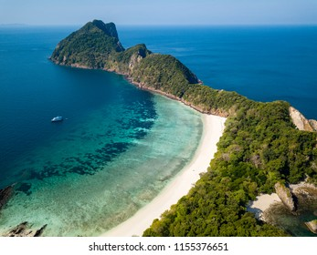 Aerial drone view of a small tropical island with lush green forest and a beautiful sandy beach with coral reef