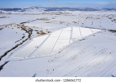 Aerial drone view of snow covered solar panel park, photovoltaic power station in the winter