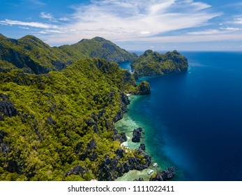 Aerial drone view of spectacular tropical scenery with towering cliffs, jungle and pristine sandy beaches