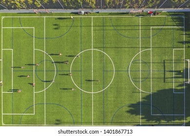 Aerial drone view from the sport center during the training of the football team. Players are playing a soccer match, aerial shot with a drone from a altitude at summer day.