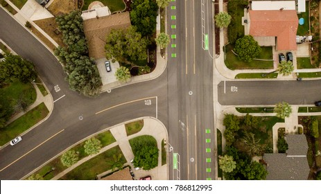 aerial drone view of a suburban neighborhood street and intersection
