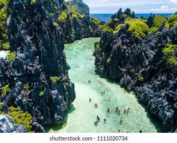 Aerial drone view of swimmers and tourists inside a beautiful, shallow tropical laggon surrounded by jagged cliffs