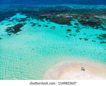 Aerial drone view of tiny tropical Mopion island sandbar, turquoise Caribbean sea and romantic couple in St Vincent and Grenadines
