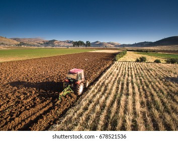 Aerial drone view of a tractor plowing fields in the andes of Huancayo, Junin, Peru.