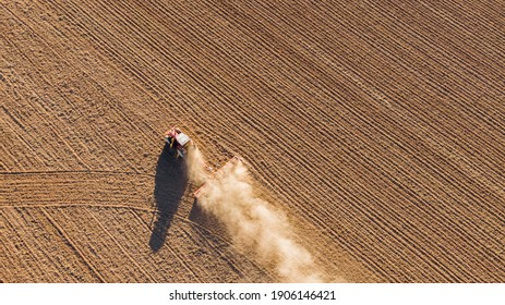 Aerial drone view of a tractor tilling the land