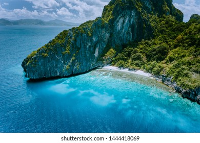 Aerial drone view of tropical Entalula Island. Huge steep rocks cliffs mountains surrounding blue bay with beautiful coral reef. Island hopping tour trip El Nido, Palawan