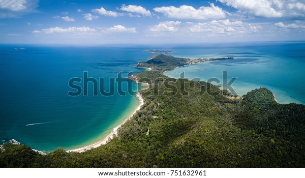 Aerial drone view of a tropical island with rainforest, white beaches and blue water in Malaysia.