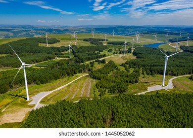 Aerial drone view of turbines at a large onshore windfarm on a green hillside (Pen y Cymoedd, Wales)