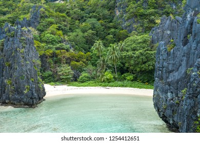 Aerial drone view of turquoise coastal waters and limestone cliffs in El Nido archipelago tourist destination of Hidden beach. El Nido, Palawan, Philippines.
