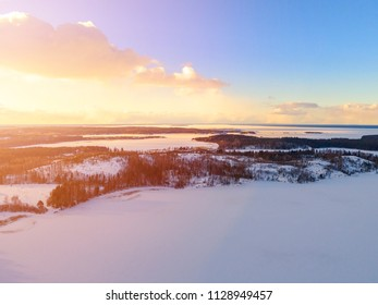Aerial drone view of a winter landscape. Snow covered forest and lakes from the top. Sunrise in  nature from a birds eye view. Aerial photography. Aerial photo. Quadcopter. Soft lighting