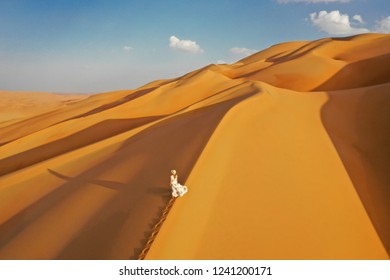 Aerial drone view of a young caucasian woman walking on massive sand dunes during sunset in the empty quarter. Abu Dhabi, UAE.