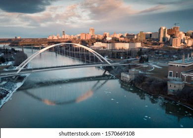 Aerial of early winter sunrise in the Edmonton River Valley. The orange glow rakes across the horizon and lights up downtown as well as the Walterdale Bridge which reflects in the Saskatchewan river.