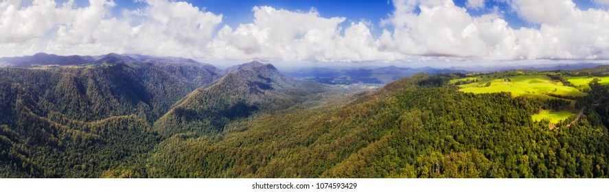 Aerial elevated panorama over Dorrigo national park main valley with mountains covered by Gondwana rainforest under blue sky on a sunny day.