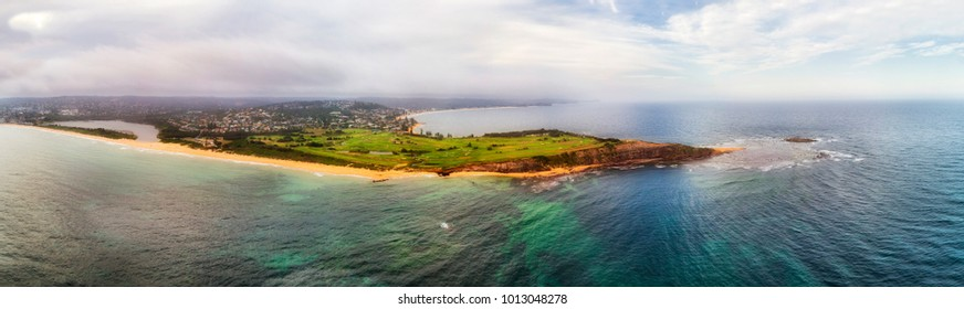 Aerial elevated panorama over waterfront betwen Mona Vale beach and collaroy beach - Long Reef headland with green field of golf course.