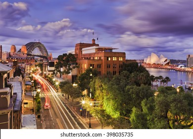 Aerial elevated view of The Rocks historic district in Sydney CBD as Sunset when bright lights illuminate city streets and landmarks.