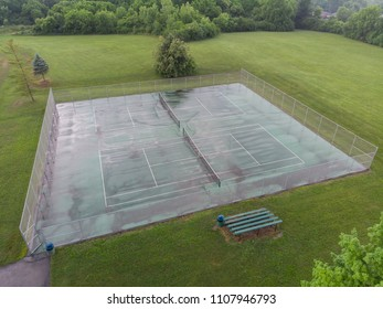 Aerial establishing shot of tennis courts after summer rainfall.