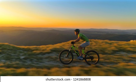 AERIAL: Extreme male cross country cyclist speeds along a scenic mountain trail at sunrise. Flying along a young man riding his bicycle down a grassy path on a picturesque sunny evening in Slovenia.