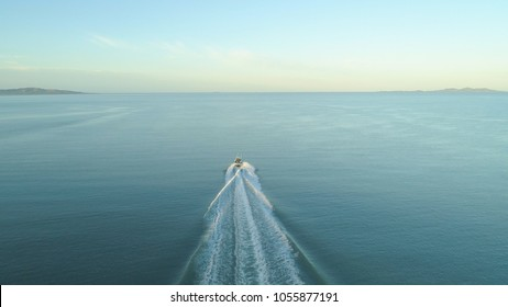 AERIAL: Fishing boat leaves a trail in the calm ocean water as it speeds towards endless horizon on a picturesque summer day. Flying behind fisherman speeding in small boat into the vast open ocean.