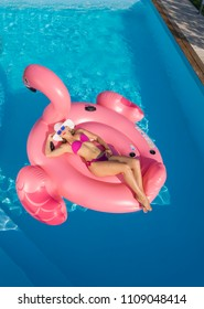 AERIAL: Flying above fit Caucasian woman lying on a floatie and sunbathing in the middle of a beautiful blue pool in her backyard. Carefree female tourist relaxing on a big pink inflatable flamingo.