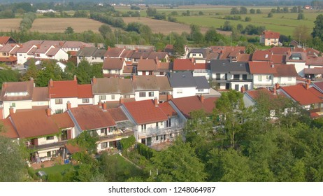 AERIAL: Flying above the quiet suburban townhouses on a sunny summer afternoon. Cool shot of terraced houses in a luxury neighborhood in Slovenia. Green nature surrounds the middle class suburbia.