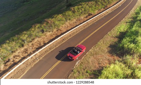 AERIAL: Flying above young couple driving the luxury red convertible car on a countryside road leading through beautiful nature in lush Hawaii island. Happy man and woman traveling on summer vacation
