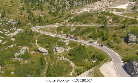 AERIAL: Flying along a steep mountain road in the sunny Dolomites and a heavy truck carrying wood climbing it. Lorry and cars slowly driving towards a mountain pass on a sunny summer day in Italy.