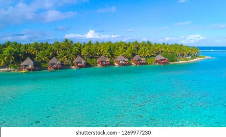 AERIAL: Flying along tropical island shoreline and luxury bungalows in breathtaking Aitutaki. Breathtaking shot from above of oceanfront villas by the palm tree forest overlooking vast turquoise sea