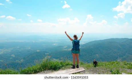 AERIAL: Flying around a cheerful girl standing at the top of a mountain with outstretched arms after hiking up a narrow trail with her little dog. Ecstatic woman trekker celebrates successful ascent.