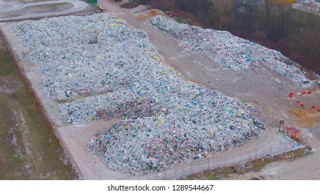 AERIAL: Flying around junkyard enclosed by a rusty fence and surrounded by trees. Circling above big heaps of junk piling up in a remote landfill. Aerial shot of a junkyard full of waste plastic.