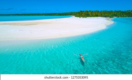 AERIAL: Flying close to young Caucasian woman swimming on her back close to the picturesque sandy beach. Young female tourist floating in the crystal clear ocean water by the lush paradise island.