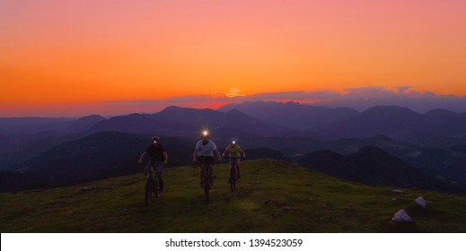 AERIAL: Flying in front of a group of mountain bikers pedalling their bikes up a steep grassy hill at night. Three friends wearing headlamps go on a cross country bicycle trip early in the morning.