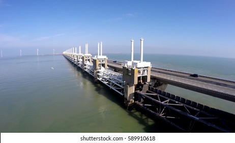 Aerial flying low and parallel west side Oosterscheldekering part of Delta Werken largest of 13 Delta Works dams and barriers English Eastern Scheldt storm surge barrier Netherlands Deltaworks