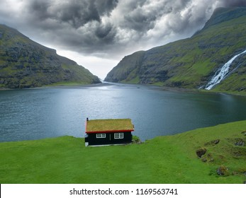 AERIAL: Flying over a small oceanfront house near the scenic steep rocky hills. Picturesque view of the beautiful coast of Faroe Islands and a lovely house in the middle of a vibrant green meadow.