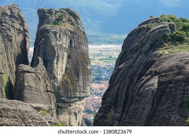 AERIAL: Flying towards a crevice splitting the two smooth towering boulders in the picturesque Greek countryside. Stunning drone view of a small Greek rural town behind two cliffs in sunny Meteora.