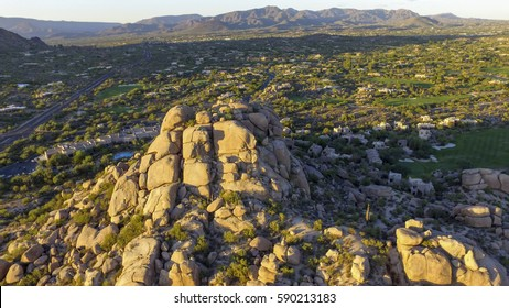 Aerial flyover of The Boulders scenic landmark rock formation and nearby golf course in Carefree, Arizona USA