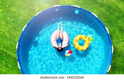 Aerial. Girl resting in a metal frame pool with inflatable toys. Summer leisure and fun concept. Frame pool stand on a green grass lawn. Top view from drone.