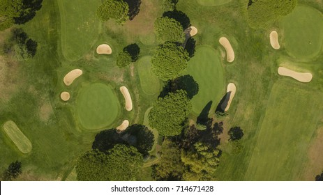 Aerial of a golf course with sand barriers, huge meadows and trees that make the game harder. The sun shines and is an ideal day for sports and outdoor activities.