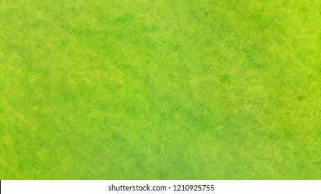 Aerial. Green grass texture background. View above from bird's eye view.