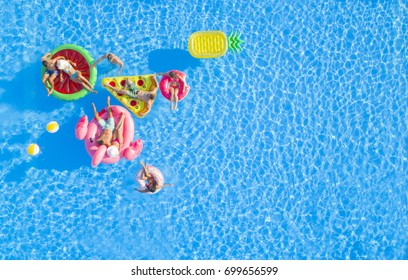AERIAL: Group of happy attractive people hanging out on fun floaties in the pool