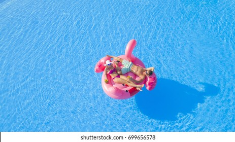AERIAL: Guy and girl relaxing, sipping cocktails on fun flamingo floatie in pool