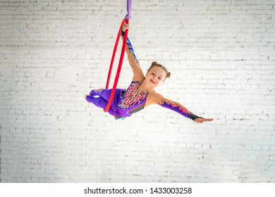 aerial gymnastics on the circle, a little girl doing exercises.