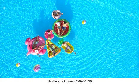 AERIAL Happy friends playing volleyball on fun inflatable floaties in pool water