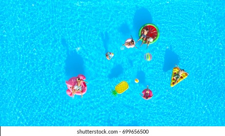AERIAL Happy young friends playing with a ball on fun colorful floaties in pool