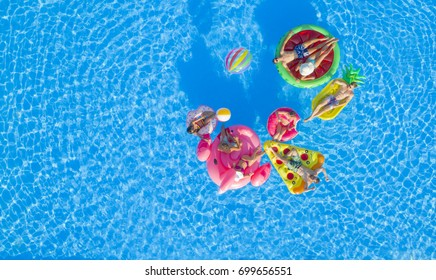 AERIAL: Happy young friends playing water volleyball on fun floaties in pool