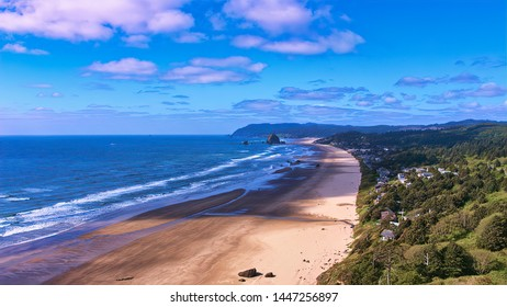 Aerial of Haystack Rock, white sandy beach, waves  blue sky with clouds