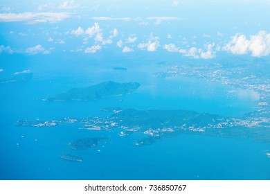 Aerial haze view of the tropical islands and town in a bay with blue sea water