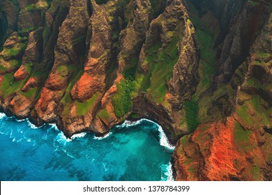 An aerial helicopter tour view of the pinnacles, cliffs, and colorful shoreline of the Na Pali Coast, located on the northwestern side of the island of Kauai, Hawaii, United States.