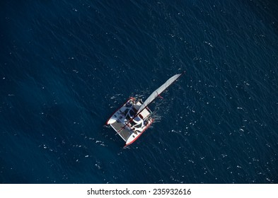 Aerial helicopter view of catamaran over deep blue sea
