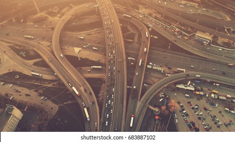 Aerial high drone flight over evening road traffic in Kiev, Ukraine. Highway and overpass with cars and trucks, interchange, two-level road junction in the big city. Top view. Vintage filter toning