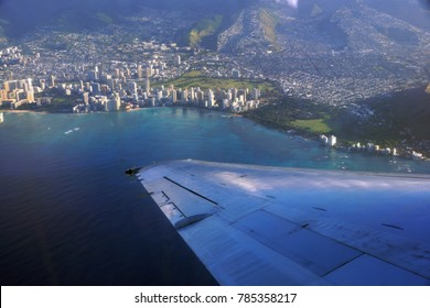 Aerial high in the sky shot of window view of plane leaving Honolulu, Hawaii with the wing of a commercial jet plane with large ship in the water and Diamondhead,